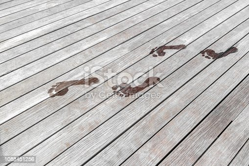 1088451256 istock photo wet footprints on a wooden terrace. 1088451256