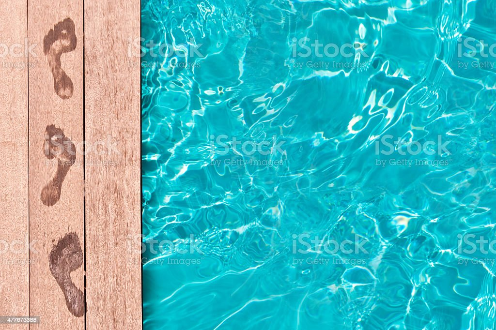 Wet footprints on the deck of a swimming pool stock photo