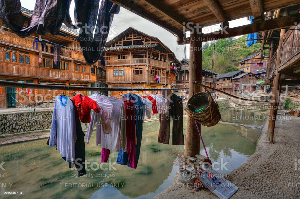 Wet laundry drying on hangers under cover outdoors, Guizhou, China. stock photo