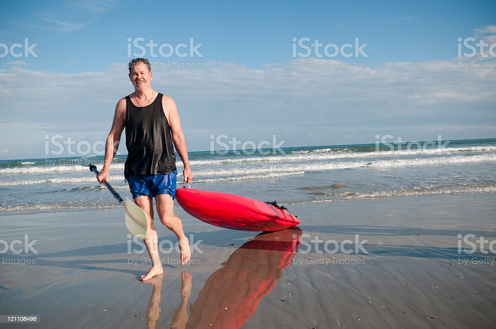 Wet man pulling red kayak out of ocean stock photo