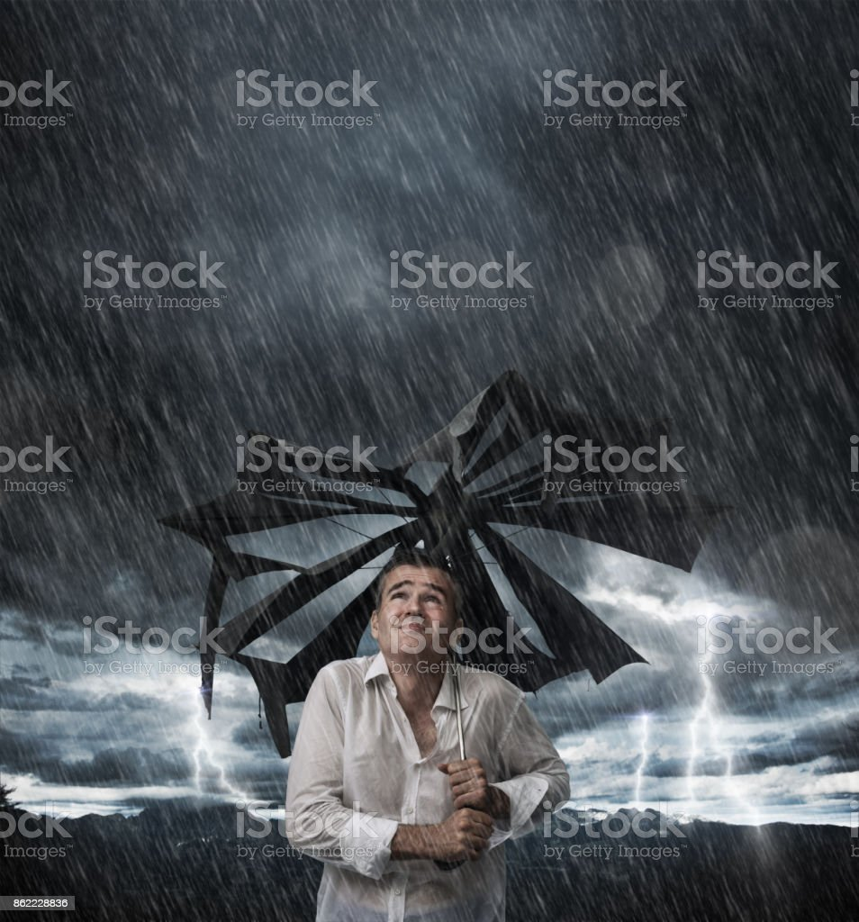 Wet man with broken umbrella stock photo