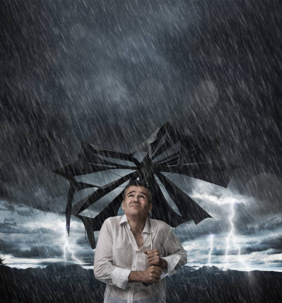 wet man with broken umbrella - drenched stock pictures, royalty-free photos & images