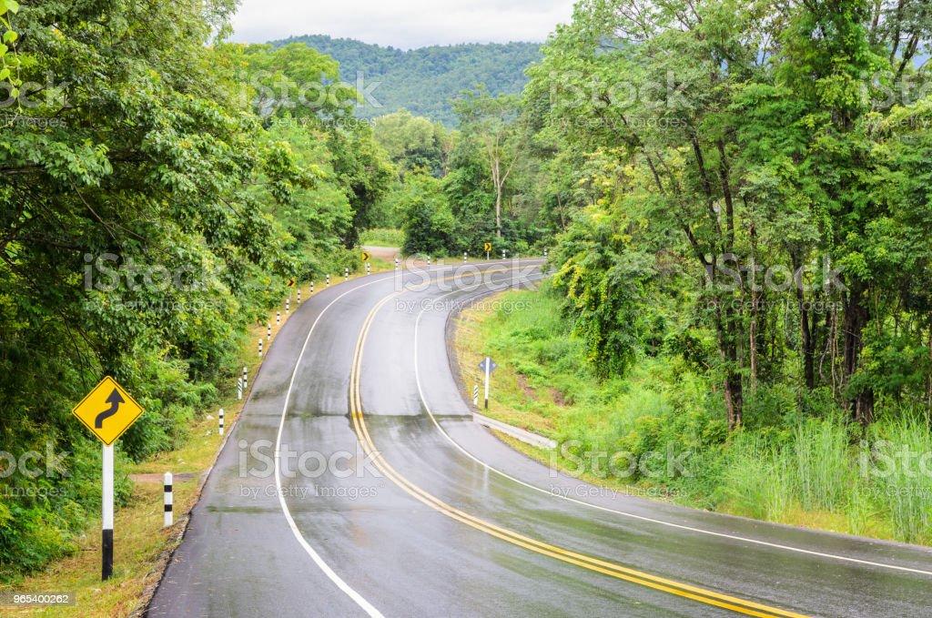 Route goudronnée de montagne humide après la pluie avec panneau de signalisation - Photo de Arbre libre de droits