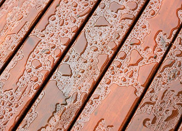 wet outdoor decking surface - houtbeits stockfoto's en -beelden