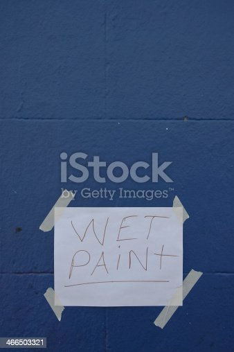 istock Wet Paint paper sign on blue wall 466503321