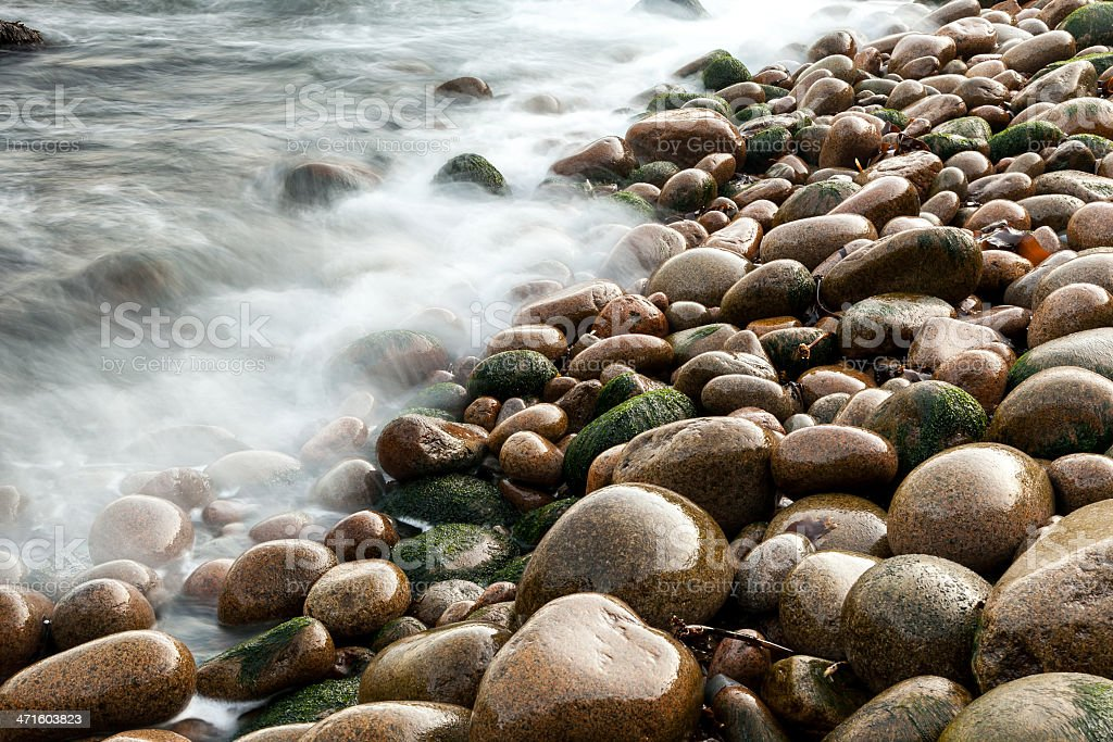 Wet pebbles on beach with blurred water, Maine, USA royalty-free stock photo