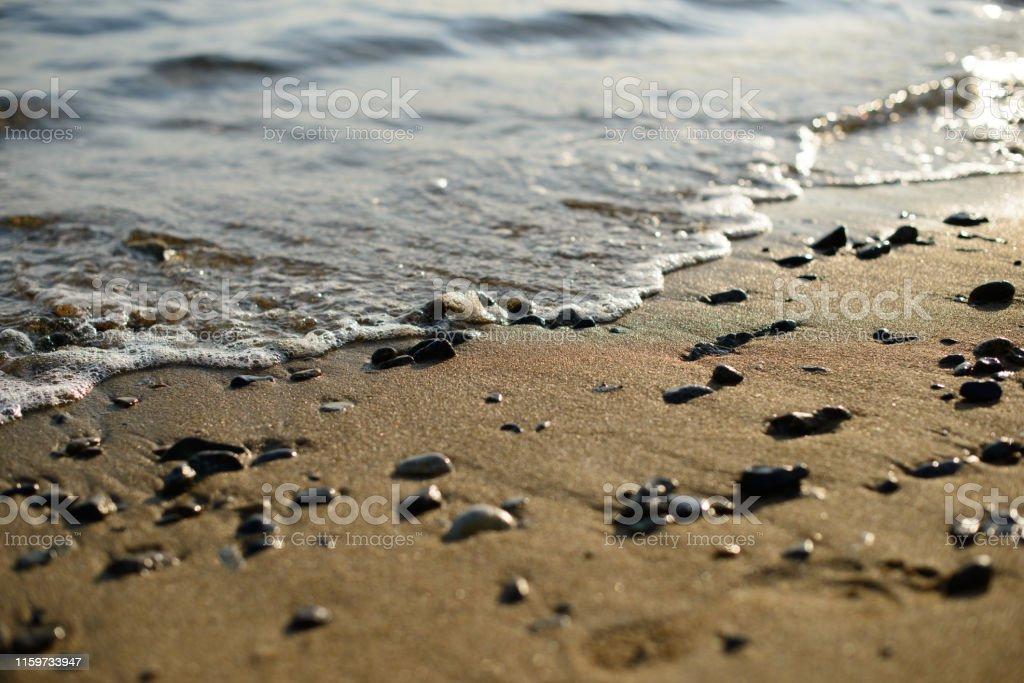 Wet pebbles on seashore in evening sun light. Sea wave on seacoast...