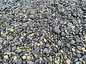High angle closeup view of wet, various coloured smooth, worn pebbles on the beach near Byron Bay north coast NSW