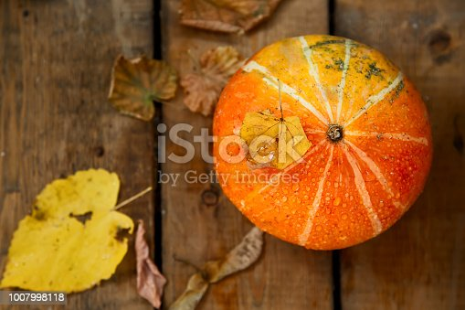 istock wet pumpkin with one dried yellow leaf in autumn wooden background 1007998118