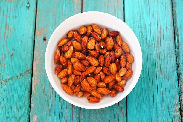 wet raw almonds on turquoise wooden table - drenched stock pictures, royalty-free photos & images