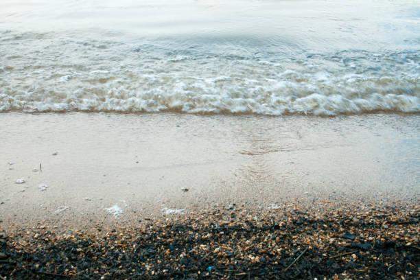 nassen sand von den wellen am ufer eines sees wald - roll tide stock-fotos und bilder