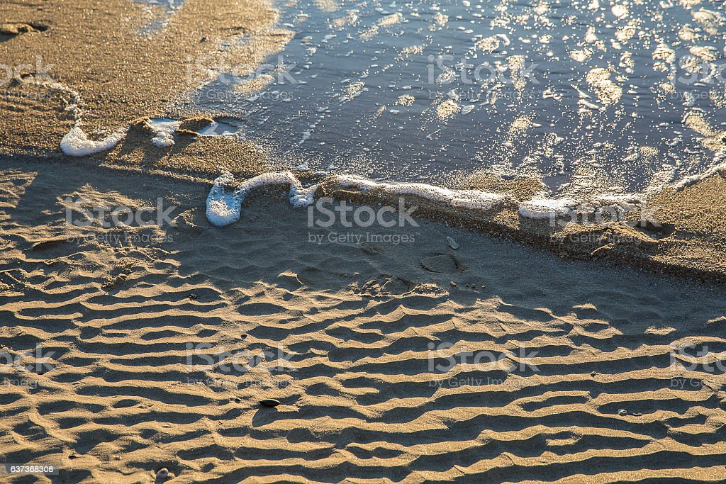 wet sand with wavy pattern and sea foam stock photo