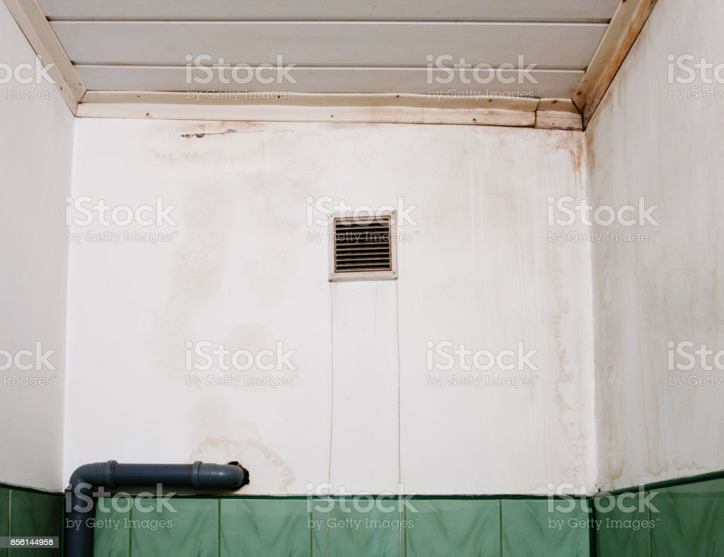 Wet stain on white wall in toilet. stock photo