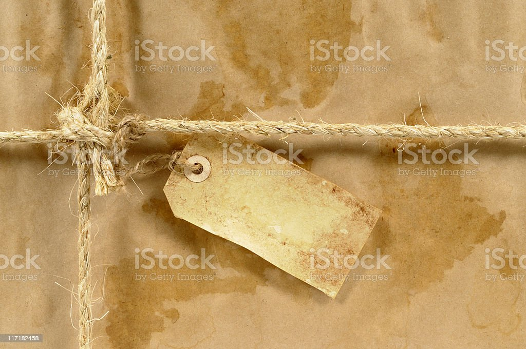 Wet stained parcel with grunge tag royalty-free stock photo