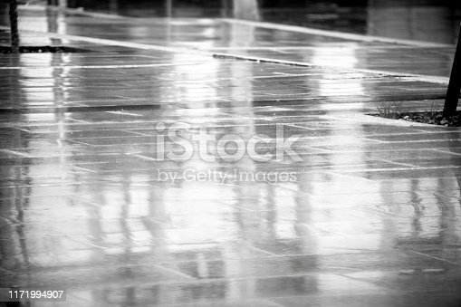 Wet street paving stone floor, building facade reflections. Black and white full frame view. A Coruña, Galicia, Spain.