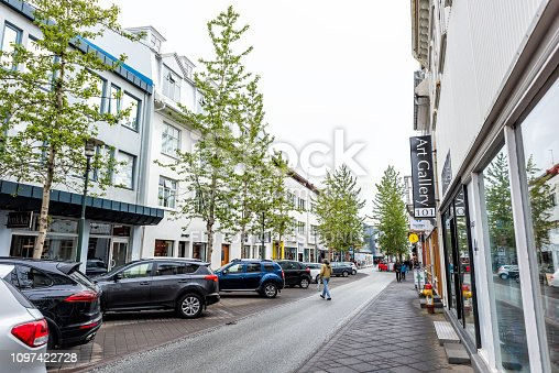 Reykjavik, Iceland - June 19, 2018: Wet street road sidewalk and parked cars in downtown center and signs for art gallery