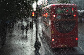 Wet mood is transmitted by this photo. The windows is focused and a double decker bus is visible behind along with a couple walking under the rain. This photo was taken in central london