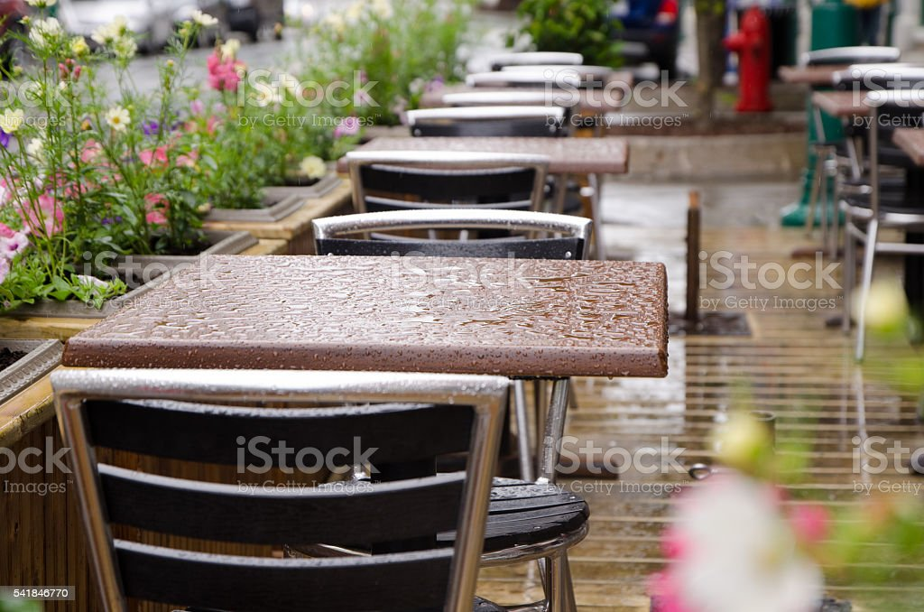 Wet table on an outside restaurant patio after rain stock photo