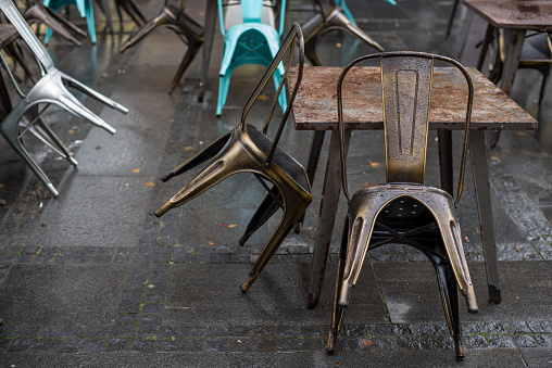 Wet tables and chairs on the city street outside the restaurant after the rain.