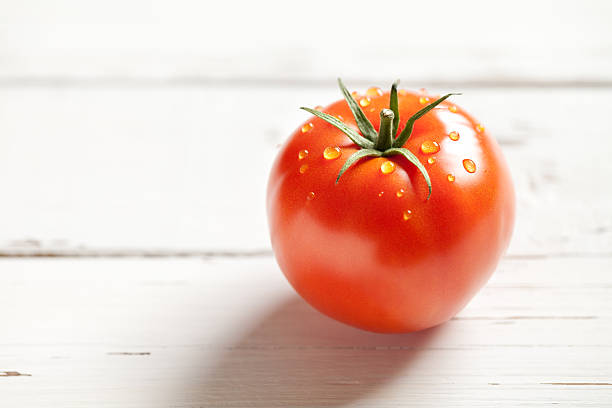 wet tomato on old wooden table - xxmmxx stock photos and pictures