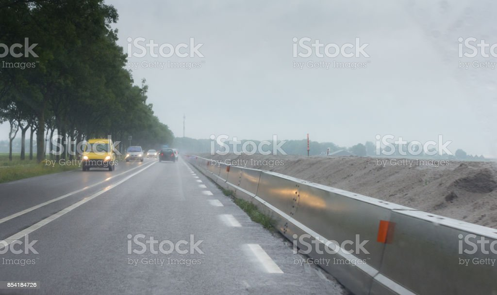 Wet weather and roadworks on country road stock photo
