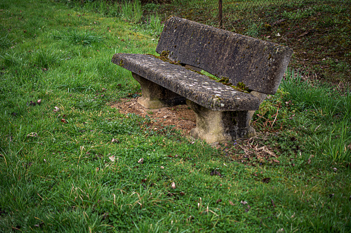 weathered stone bench in  the rain