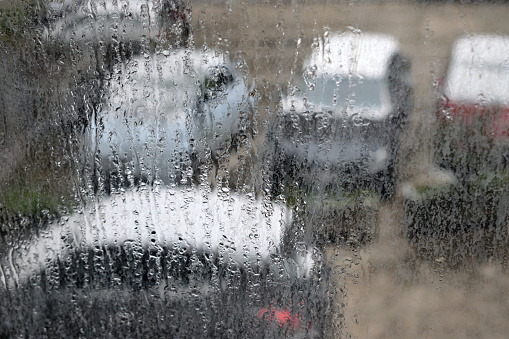 wet windows with a cars covered by snow in the background