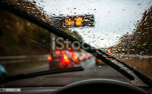 Wipers clearing rain, and roads busy with traffic as the light fades on a winter commute.