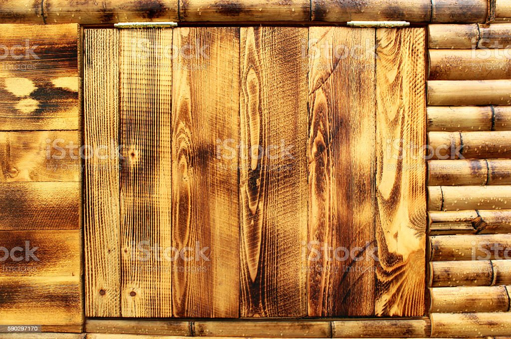 Wet yellow brown closed wooden door in bamboo wall royaltyfri bildbanksbilder
