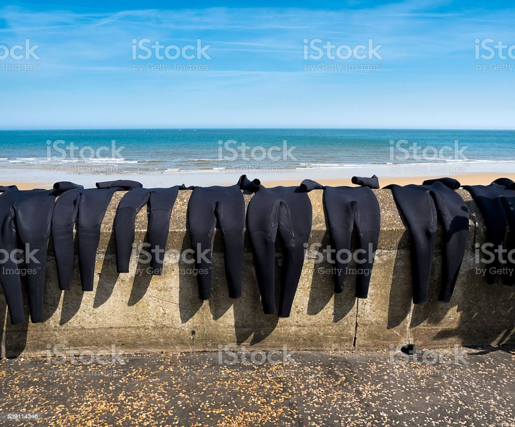 Wetsuits drying on a promenade wall stock photo