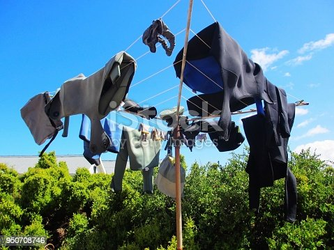 Some wetsuits hanging on a washing line to dry.