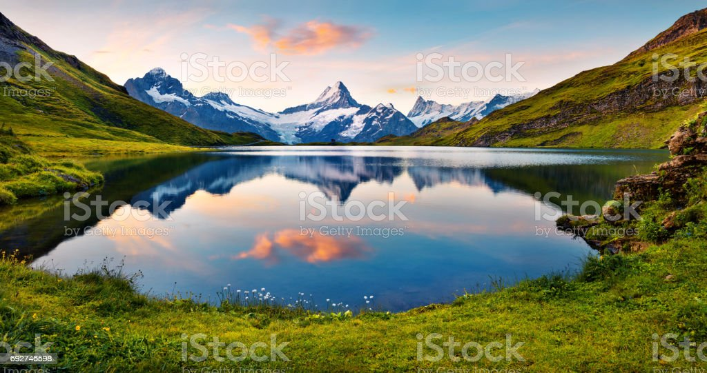 Wetterhorn and Wellhorn peaks reflected in water surface of Bachsee lake stock photo