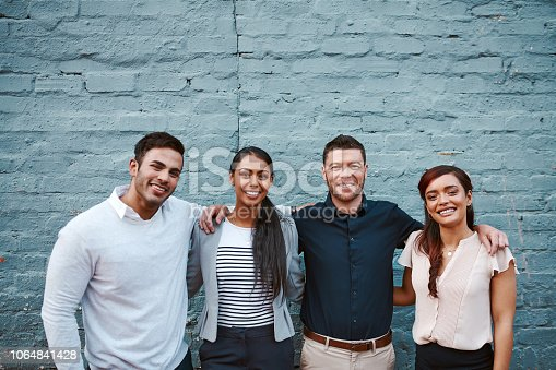 Portrait of a group of businesspeople standing together against a grey wall outside
