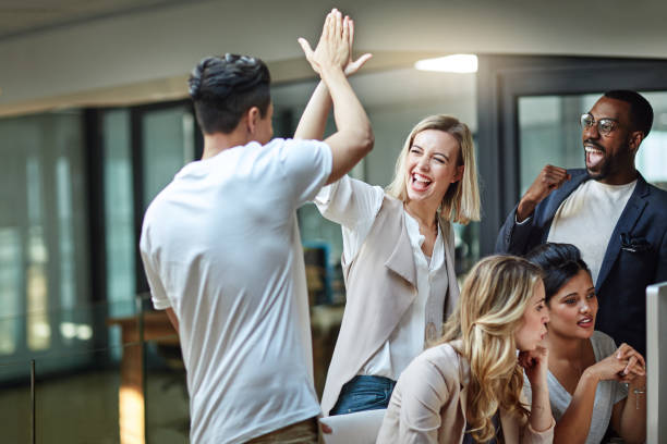 We've done it again! Shot of a group of colleagues giving each other a high five while using a computer together at work achievement stock pictures, royalty-free photos & images