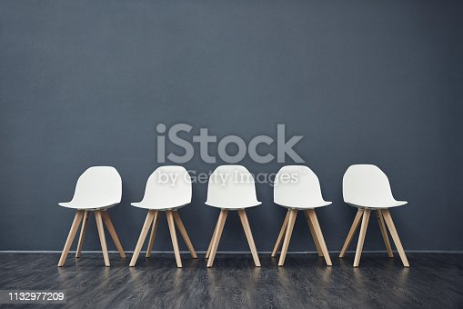 Shot of a row of empty chairs against a grey background inside of a studio