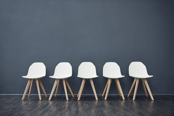 We've got spots available Shot of a row of empty chairs against a grey background inside of a studio chair stock pictures, royalty-free photos & images