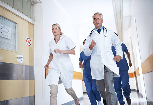 We've got to get to the patient ASAP! Shot of a determined medical team running down a hospital corridor for an emergency ASAP stock pictures, royalty-free photos & images