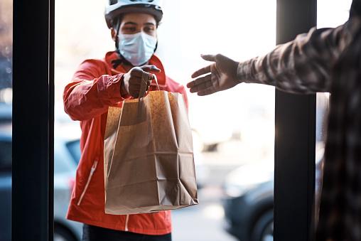 Shot of a masked man delivering a food package