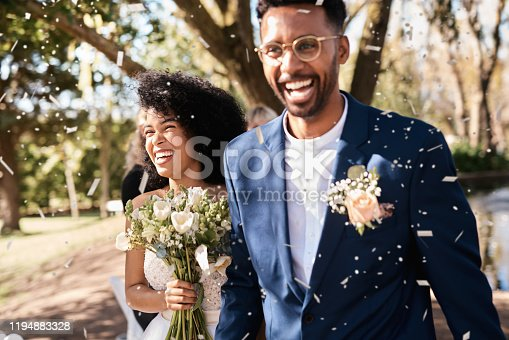Shot of a happy newlywed young couple getting showered with confetti outdoors on their wedding day