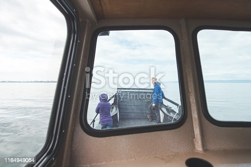 A small whalewatching boat heads out off the Alaska coastline to look for humpbacks. The shot is through the cabin window of two passengers standing on the bow.