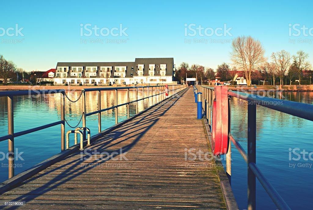 Wharf scaffold above  sea at harbor. Big house on coast stock photo