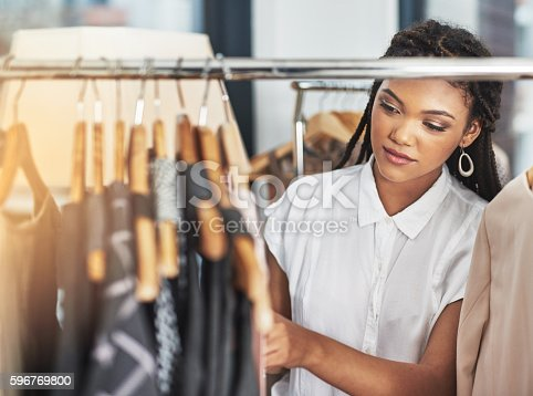 Cropped shot of a woman looking at clothes on a rail in a store