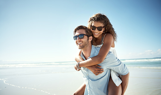 Shot of a young man piggybacking his girlfriend on the beach
