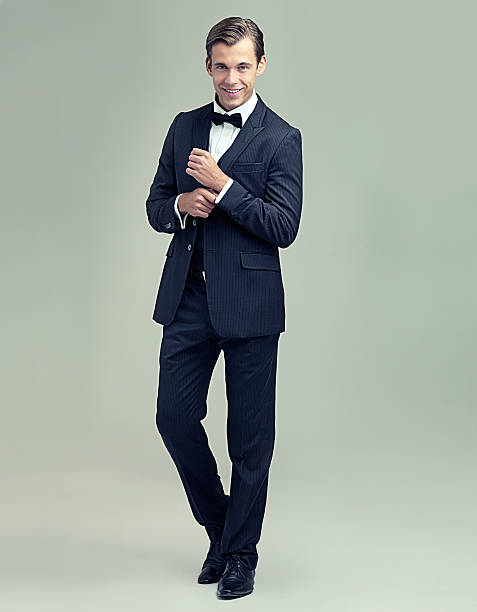 What a dapper gentleman A full length studio portrait of a stylish young gentleman giving a charming smile tuxedo stock pictures, royalty-free photos & images