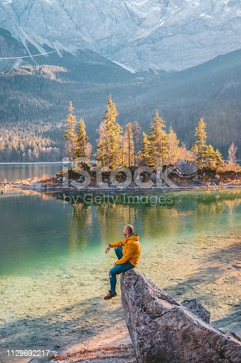 Photo of Traveler Man relaxing meditation with serene view mountains and lake landscape Travel Lifestyle hiking concept summer vacations outdoor. Male dreamer, sitting on the Ibsen lake edge in Germany at sunset, human strength, psychology concept. Men Wearing Jacket sitting on rock during autumn day and looking away.