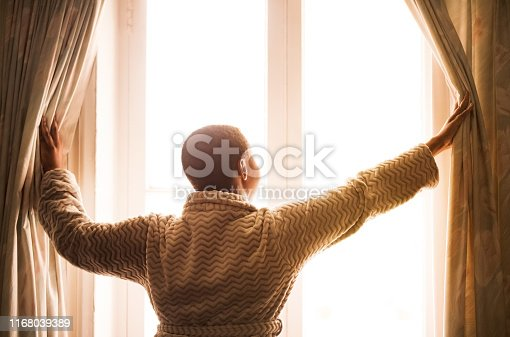 Rear view shot of a young woman opening the curtains in the morning to get fresh air