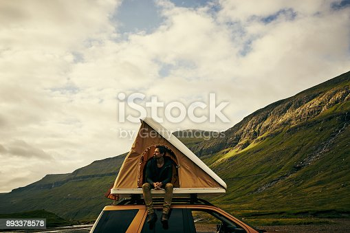 Shot of a cheerful young man sitting in his tent that he assembled on top of his car outside in nature