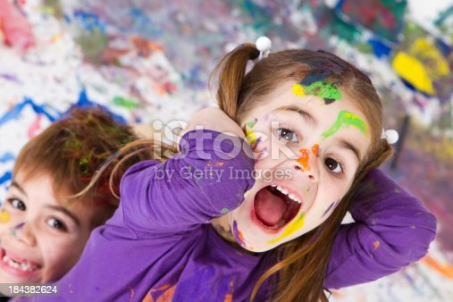 Cute little sister and his brother shouting with a mess background