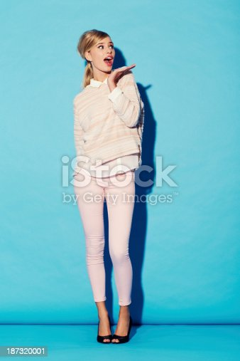 A gorgeous young retro beauty wearing a surprised expression while posing with her hand next to her face