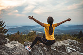 Girl sitting on a green meadow and watching the countryside landscape at evening landscape with arms raised in southern Germany on the Feldberg 1493m. the highest mountain in the state of baden-württemberg.